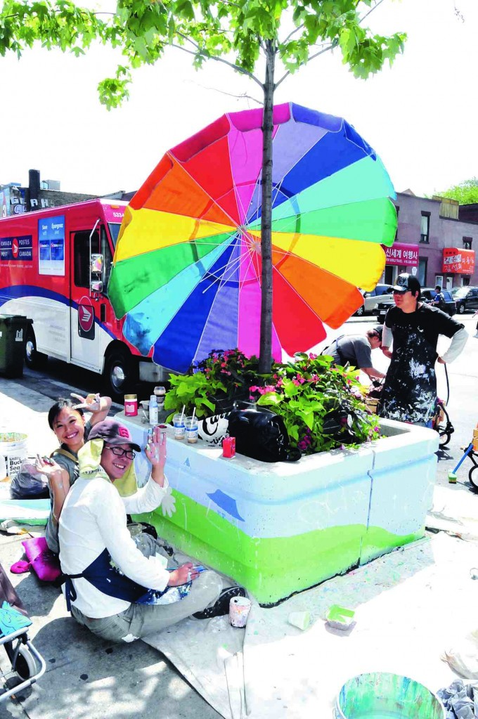 It puts a smile on our face, yes it do ... Art students Nari Heo, left waving, and Young Wook Lee are two members of S.Y.S.N, a design group of art students who volunteered to help the Koreatown BIA paint dozens of planters along Bloor Street.