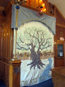 Designed by congregant Dianne Saxe and embroidered by Israeli-Canadian artist Tova Raz, the synagogue's ark curtain draws on traditional symbols of Jewish life to emphasize the high value the congregation places on gender egalitarianism. The Book of Psalms inspires the central imagery, in which a tree planted by flowing water symbolizes how a Torah-centred life gives a pious Jew the strength to flourish. In the curtain, the intertwining trunks of the tree represent the interwoven male and female aspects of the congregation.