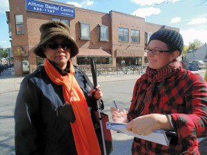 Kelsey Carriere (right) interviews a legally-blind member of a tandem bicycling club that travels along Harbord Street. Carriere is part of the team studying the demographics of Bloor Street West between Shaw and St. George streets before and after the installation of a pilot bike lane in April 2016. Summer Reid, Gleaner News