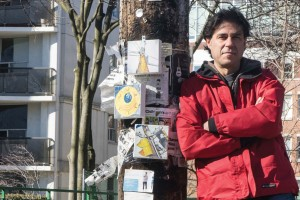 Artist Jorge Molina poses on Walmer Road with some of his work. He is installing 416 canvases on utility poles throughout the city as part of his 416 Project. NEILAND?BRISSENDEN/GLEANER NEWS