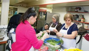 PHOTO BY GEREMY BORDONARO: In the first Annex Newcomer Kitchen event, Syrian women make maqlooba with fattoush in Butler's Pantry. Organizers hope the initiative will spread to other parts of the city.