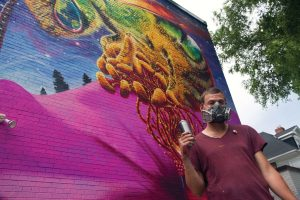 "PHOTO BY GEREMY BORDONARO/GLEANER NEWS: The June 23 unveiling of Nick Sweetman's mural on the east wall of 442 Bloor St. W. coincided with the proclamation that Toronto is now the first official Bee City in Canada. Commissioned by Burt's Bees, Sweetman's mural — which features the female metallic green sweat bee responsible for a large amount of pollination — is intended to demonstrate the bee's importance, and how we, on earth, says the artist, ""are the single house on the block"" with only one earth to keep healthy."