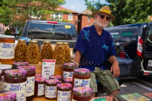 PHOTO BY GEREMY?BORDANARO/GLEANER?NEWS: Doug Eiche (background) sells his honey at the Bloor-Borden Farmers' Market. An initiative of the Harbord Village Residents' Association, the market runs every Wednesday until Oct. 19 from 3 to 7 p.m. out of the Green P parking lot just south of Bloor Street between Borden and Lippincott streets. The market's 22 stalls also offer bread, vegetables, meats, wines, and fruits from a variety of producers.